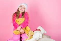 Het spel van het jong geitjemeisje met zachte stuk speelgoed teddybeer roze achtergrond Unieke gehechtheid aan gevulde dieren Kin stock foto's