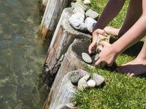 Het spel van kinderen` s handen met stenen op het water royalty-vrije stock fotografie