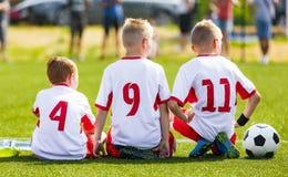 Het Spel van het voetbalvoetbal voor Kinderen De spelers die van het jonge geitjessubstituut op een bank zitten royalty-vrije stock afbeeldingen