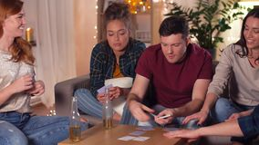 Het spel van vriendenspeelkaarten thuis in avond stock footage