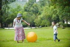 Het spelbal van de moeder en van de zoon in gras Stock Fotografie