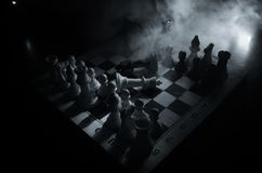 het spelconcept van de schaakraad bedrijfsideeën en de concurrentie en strategieideeën concep Schaakcijfers aangaande een donkere Royalty-vrije Stock Foto