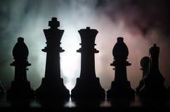 het spelconcept van de schaakraad bedrijfsideeën en de concurrentie en strategieideeën concep Schaakcijfers aangaande een donkere Stock Fotografie