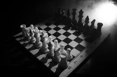 het spelconcept van de schaakraad bedrijfsideeën en de concurrentie en strategieideeën concep Schaakcijfers aangaande een donkere Royalty-vrije Stock Afbeeldingen