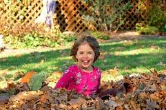 Het spelen in de bladeren Stock Afbeeldingen