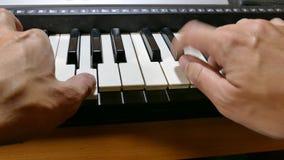 Het spelen de piano van de de synthesizermuziek van de mensenhand stelt over sleutels in werking stock video