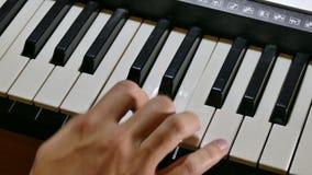 Het spelen de synthesizerhand van de mensenpiano over sleutels in werking die wordt gesteld die stock footage