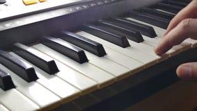 Het spelen de synthesizerpiano van de mensenhand over sleutels in werking die wordt gesteld die stock video