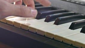 Het spelen de synthesizerpiano van de mensenhand over sleutels in werking die wordt gesteld die stock footage