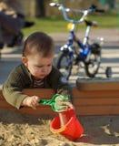 Het spelen in de zandkuil Stock Foto's