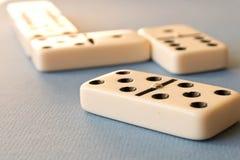 Het spelen domino's op een blauwe achtergrond Dominoconcept stock afbeelding