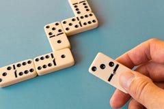 Het spelen domino's op een blauwe achtergrond Mensen` s hand met een Domino royalty-vrije stock fotografie