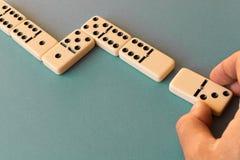 Het spelen domino's op een blauwe achtergrond Mensen` s hand met een Domino royalty-vrije stock afbeelding