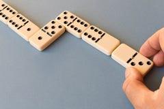 Het spelen domino's op een blauwe achtergrond Mensen` s hand met een Domino royalty-vrije stock foto's