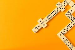 Het spelen domino's op een gele lijst Rode stukken die, ge?soleerda op witte achtergrond neer vallen stock foto