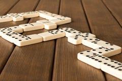 Het spelen domino's op een houten lijst Het concept de Domino GA stock fotografie