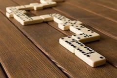 Het spelen domino's op een houten lijst Het concept de Domino GA stock afbeeldingen