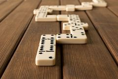 Het spelen domino's op een houten lijst Het concept de Domino GA stock afbeelding