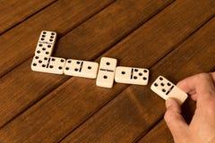 Het spelen domino's op een houten lijst Mensen` s hand met een Domino stock foto