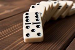 Het spelen domino's op een houten lijst Rode stukken die, geïsoleerda op witte achtergrond neer vallen royalty-vrije stock afbeelding