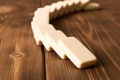 Het spelen domino's op een houten lijst Rode stukken die, geïsoleerda op witte achtergrond neer vallen royalty-vrije stock fotografie