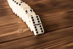 Het spelen domino's op een houten lijst Rode stukken die, geïsoleerda op witte achtergrond neer vallen royalty-vrije stock afbeeldingen