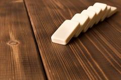 Het spelen domino's op een houten lijst Rode stukken die, geïsoleerda op witte achtergrond neer vallen stock foto