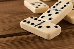 Het spelen domino's op een houten lijst Rode stukken die, ge?soleerda op witte achtergrond neer vallen royalty-vrije stock foto