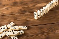 Het spelen domino's op een houten lijst Rode stukken die, ge?soleerda op witte achtergrond neer vallen stock foto
