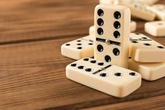 Het spelen domino's op een houten lijst Rode stukken die, ge?soleerda op witte achtergrond neer vallen royalty-vrije stock afbeelding