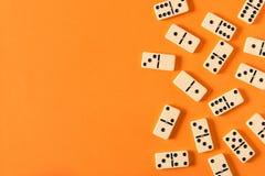 Het spelen domino's op een oranje lijst Rode stukken die, ge?soleerda op witte achtergrond neer vallen stock afbeeldingen