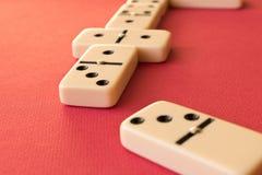 Het spelen domino's op een rode achtergrond Dominoconcept royalty-vrije stock foto's