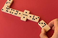 Het spelen domino's op een rode achtergrond Mensen` s hand met een Domino royalty-vrije stock foto's