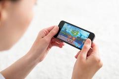 Het spelen gaan de Boze Vogels mobiel spel Stock Foto