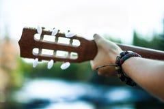 Het spelen gitaar door de rivier stock foto's