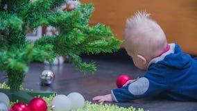 Het spelen met Kerstmisdecoratie onder een boom stock videobeelden