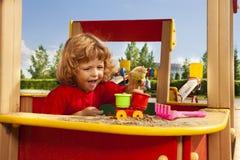 Het spelen met zand op speelplaats Stock Foto's