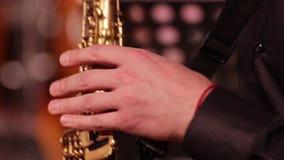 Het spelen op een houten saxofoon van de blaasinstrumentdiscant Close-up De musicus wint de geluiden van muziek door de sleutels  stock video