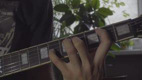 Het spelen snaren op elektrische gitaar stock footage