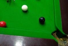 Het spelen snooker die, die de rode bal, zwarte doordringen, de bal streven en het gat in eigen zak steken om punten te noteren stock foto