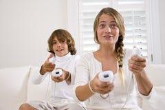 Het spelen van de broer en van de zuster videospelletjes Stock Foto's