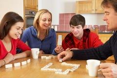 Het Spelen van de familie Domino's in Keuken Stock Afbeeldingen