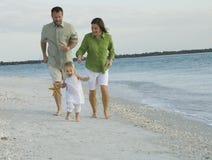 Het spelen van de familie op strand stock foto's