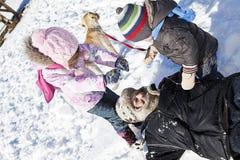 Het spelen van de familie in sneeuw Stock Foto