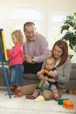 Het spelen van de familie in woonkamer Stock Foto