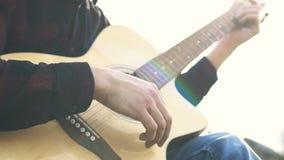 Het spelen van de gitaar Speelmuziek op een akoestische gitaar koorden stock videobeelden