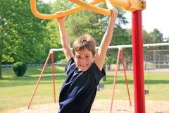 Het Spelen van de jongen bij de Speelplaats Royalty-vrije Stock Afbeeldingen