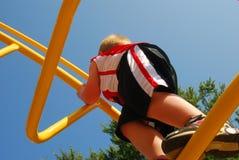 Het spelen van de jongen bij speelplaats Royalty-vrije Stock Foto's