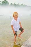 Het spelen van de jongen in de fontein Stock Afbeeldingen
