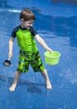 Het Spelen van de jongen in de Nevel van het Water Stock Foto